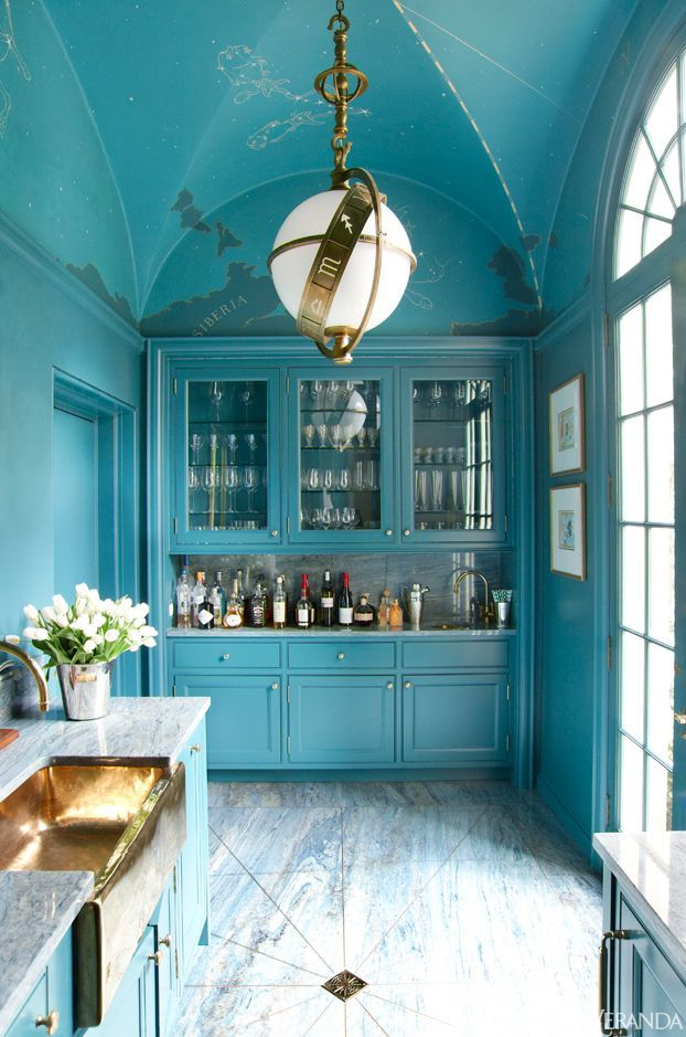 Teal color on the ceiling and cabinets creates visual interest.