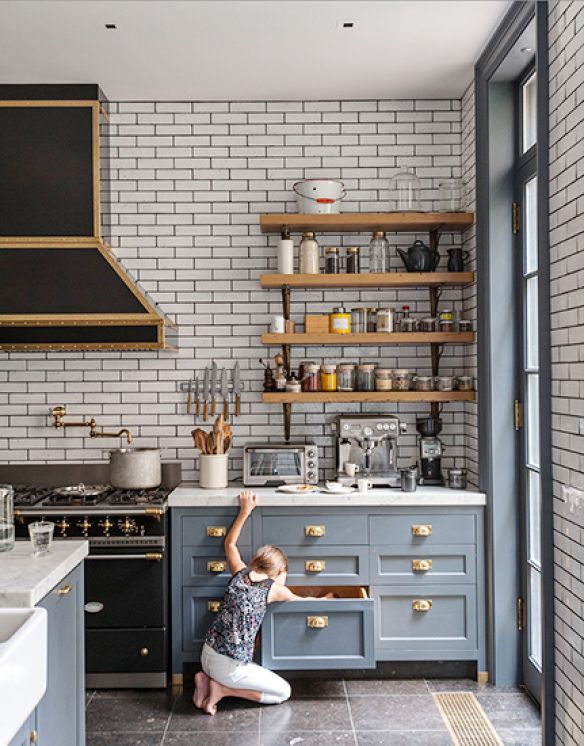 A bespoke kitchen---functional, organized and fashionable. Love the black vintage ranged with brass trim, subway tile and open shelves.
