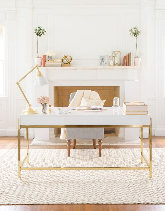 a-cozy-neutral-home-office-with-a-faux-fireplace-a-white-and-gold-desk-and-lamp-potted-greenery-and-a-printed-rug-plus-a-chair