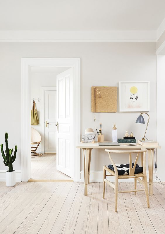 a-cozy-neutral-home-office-with-some-wooden-furniture-art-on-the-wall-and-a-cactus-in-a-pot