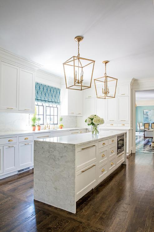 gold-lanterns-over-long-marble-waterfall-kitchen-island