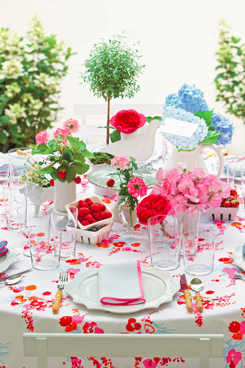elegant outdoor tablescape with red floral tablecloths and fresh garden blooms