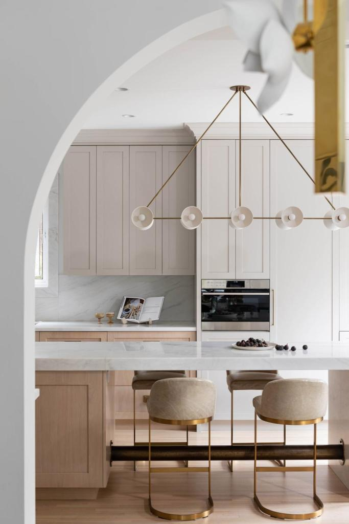 a modern kitchen with white-wash cabinetry and brass bar stools