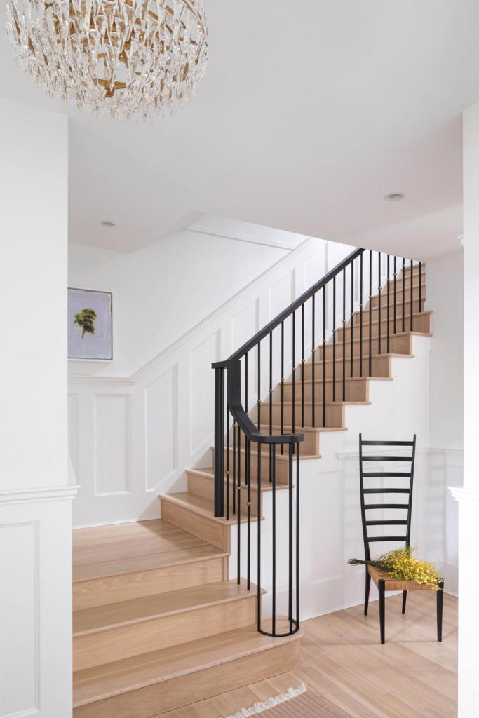 warm and inviting entry with light wood stairs and flooring