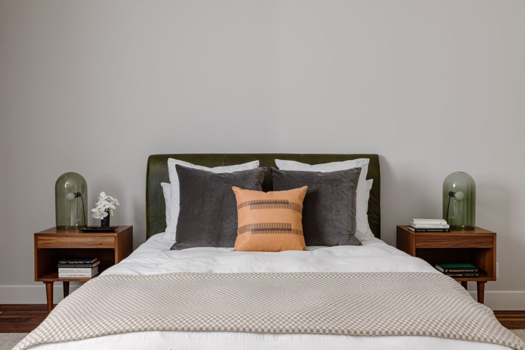 mid-century modern furnishings are calming while the wood and the pop of orange make this guest bedroom warm and inviting.