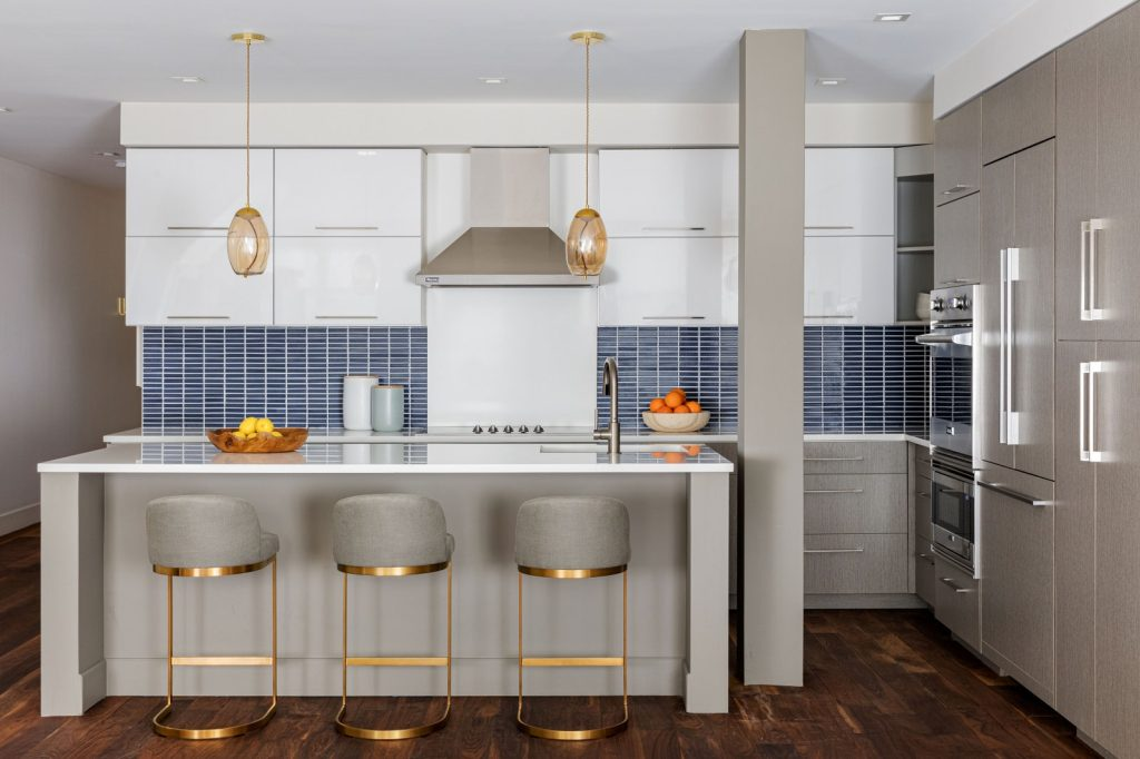 The brass frames on the stylish bar chairs inject a dose of glam into this white kitchen