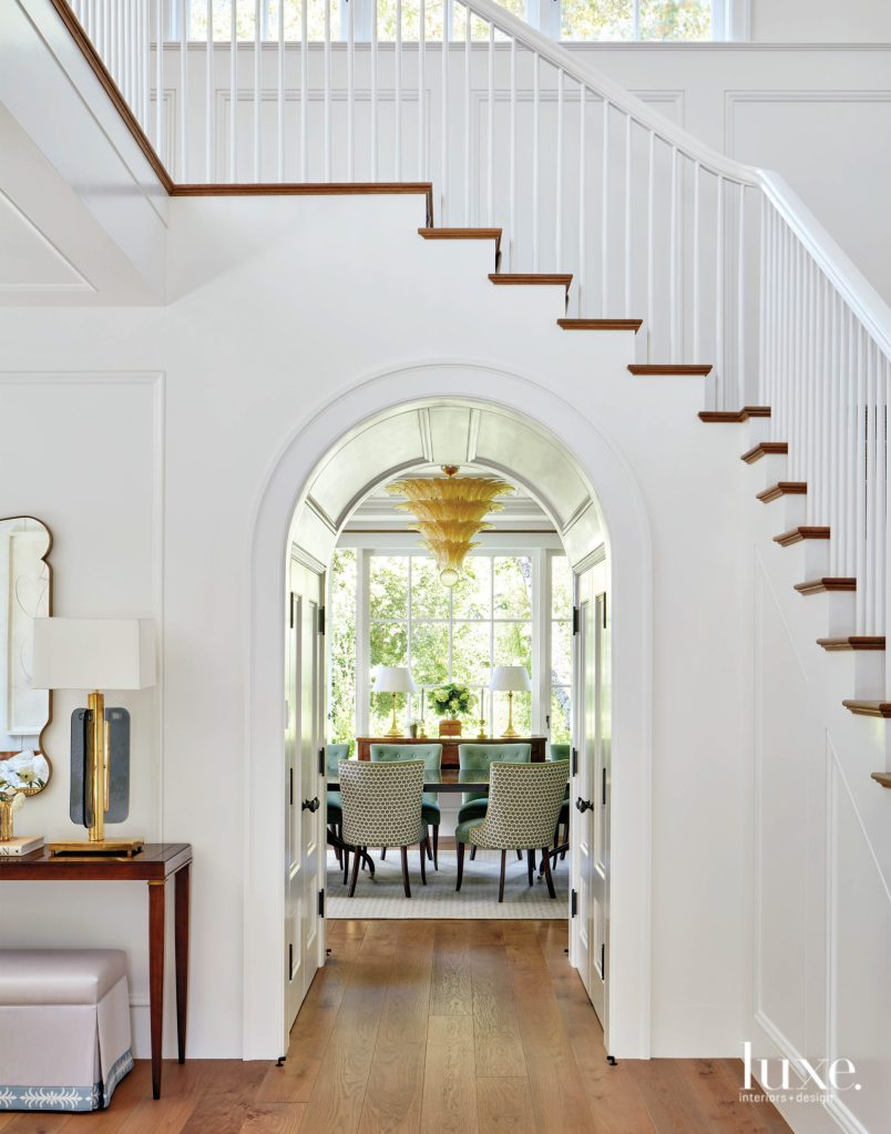 The hallway gives glimpse of the dining room with big windows in the far end. The chandelier, the clean-lined classical rosewood console, the gilded table lamps and the skirted ottoman emphasizes the sophistication vibes of the home.