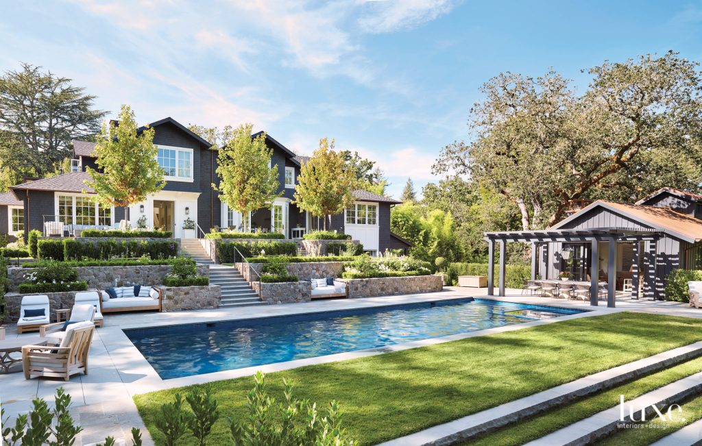 The lush pool area dotted with stylish outdoor furniture