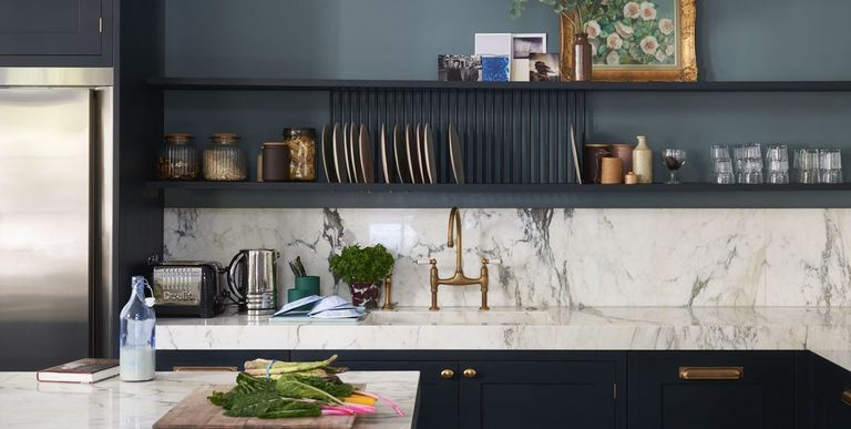emerald green cabinetry and creamy marble countertops and backsplash