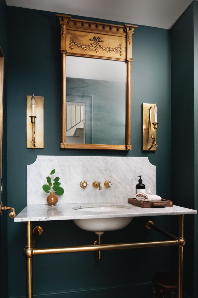 The dark green wall and the brass-framed vanity
