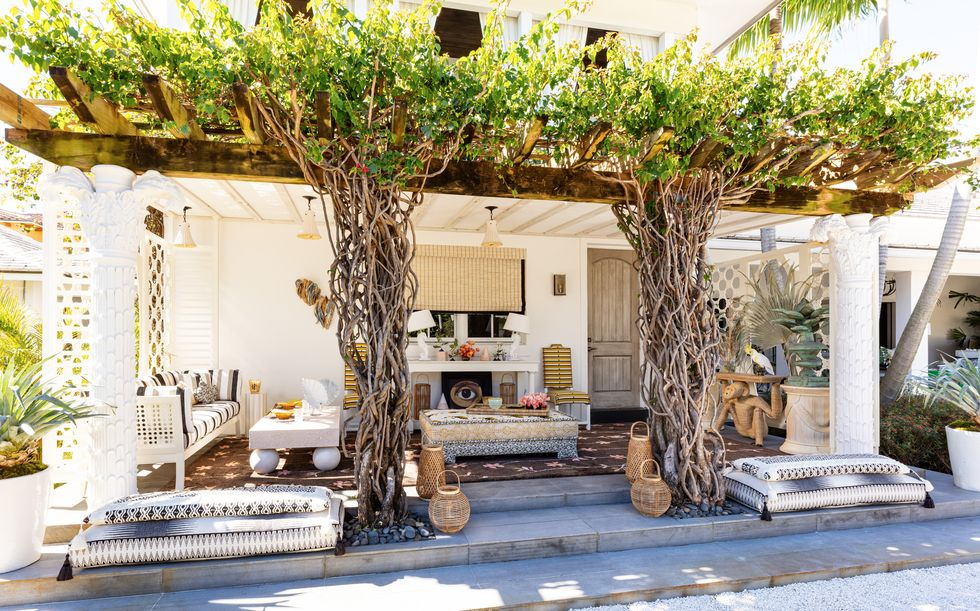 outdoor living area with the plush cushions with exotic textiles, the natural-fiber lanterns, the wood console