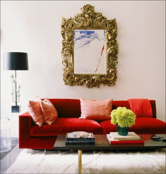 An antique gilded mirror over a red modern sofa crteates a timeless design