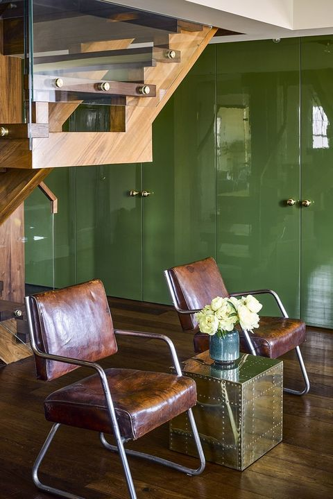 The green lacquering walls bring in a touch of glam to this mid-century modern living room