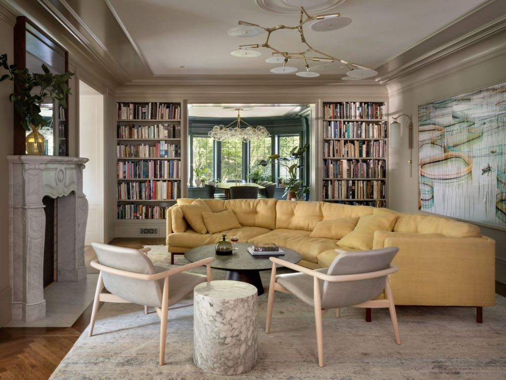 A Yellow Curved Sofa Is A Focal Point Of This Living Room
