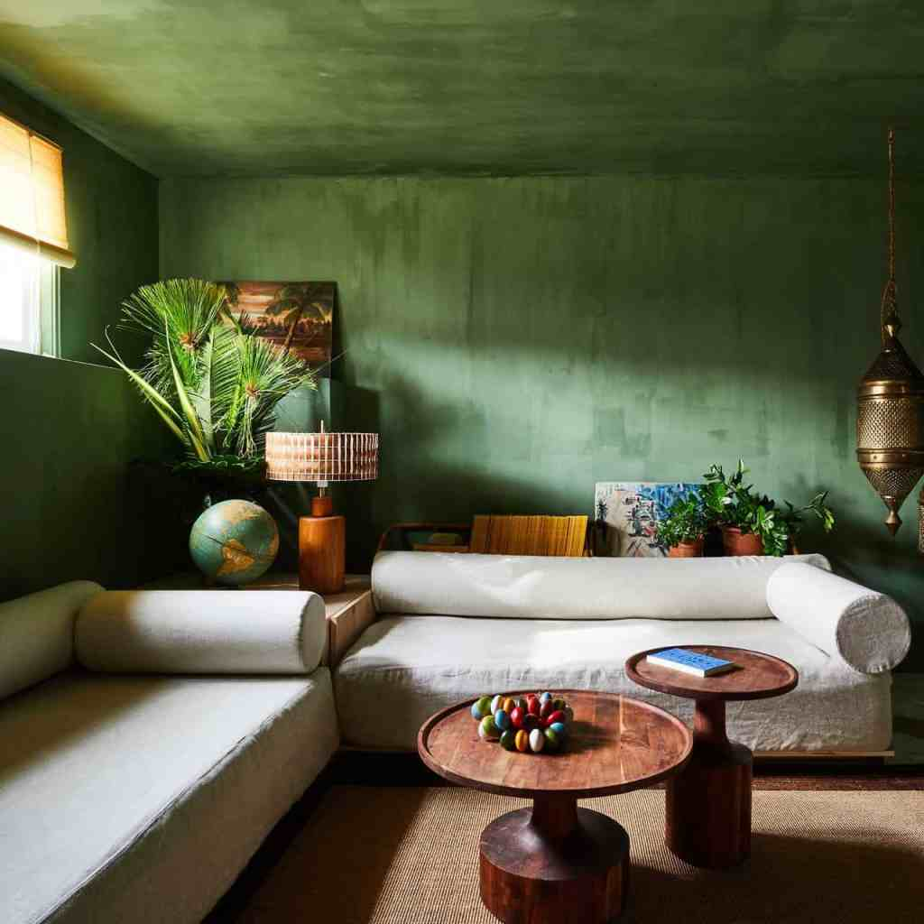 green plaster walls envelops this living room with a cozy vibe