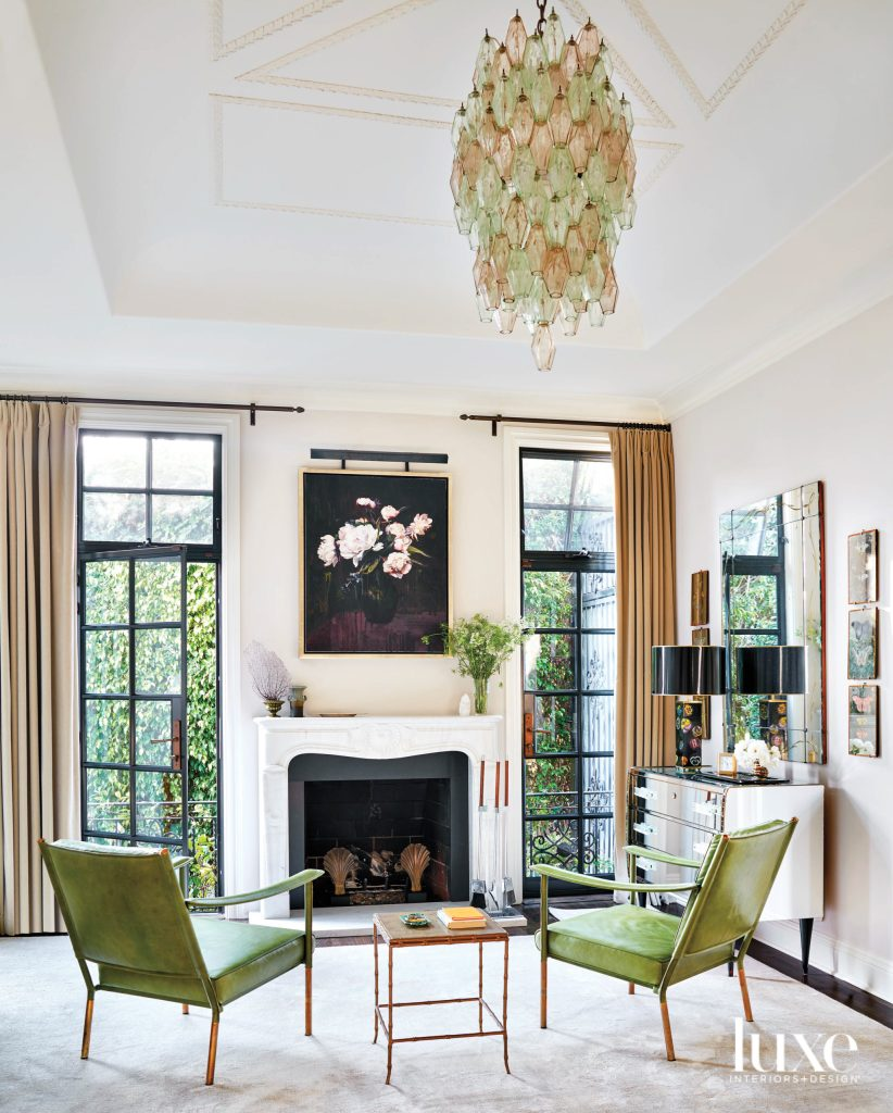 green on the lounge chairs by the fireplace is soothing and elegant and echos green outside. The marble mantle adds a classical vibe to the living space. The light brown and green chandelier makes a statement in a very subtle way.