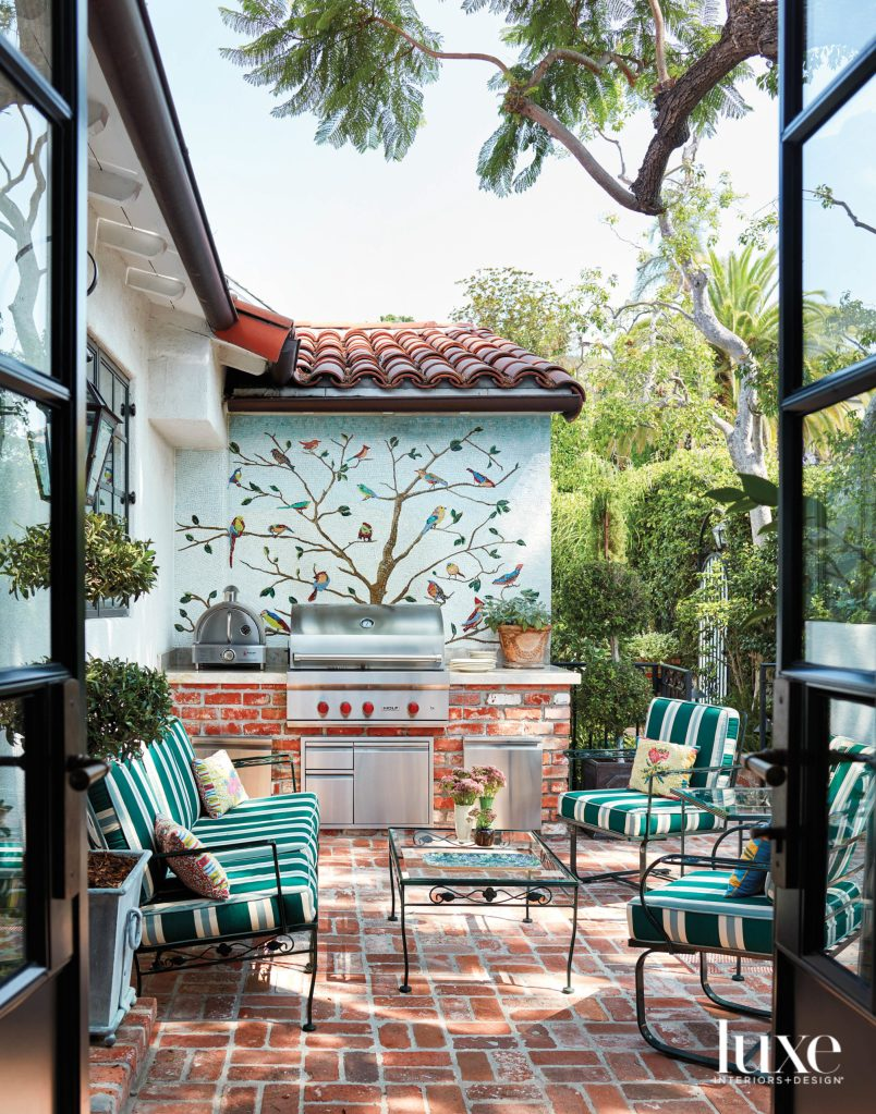 The mosaic design on the wall is intricate and interesting. The red bricks have a relaxing and casual vibe while the the newly updated fabric on the chairs and sofa  is eye-catching and  fresh. You can click here to see more ideas for outdoor living.
