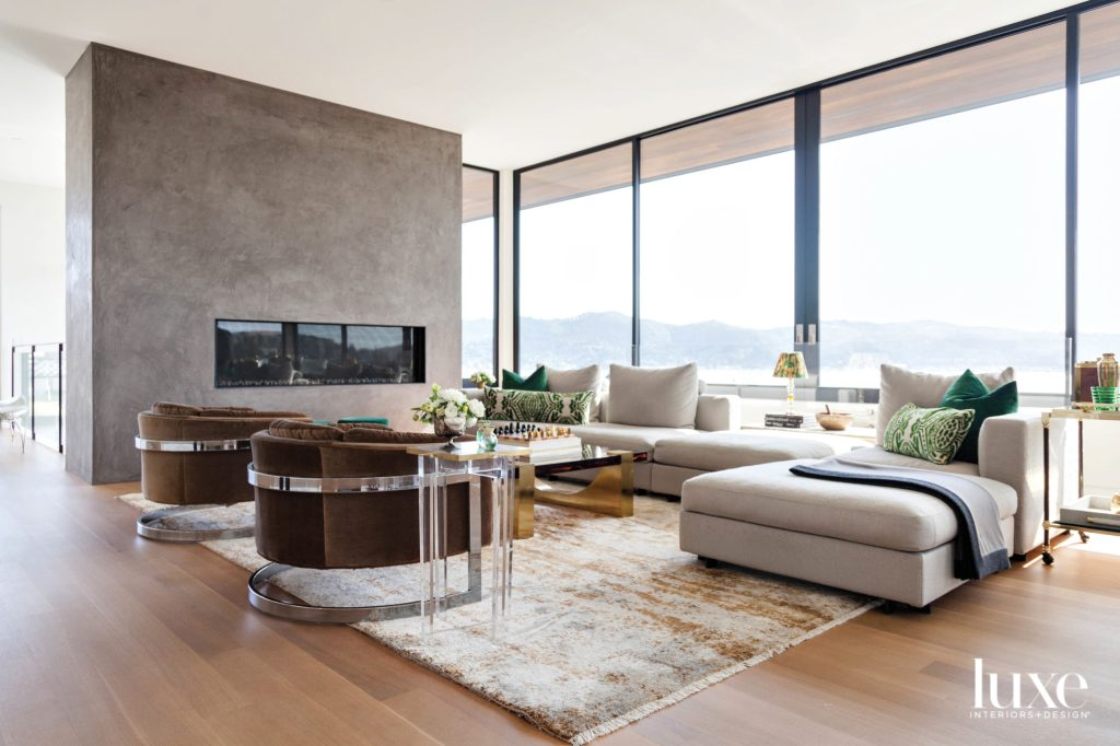 modern living room features a cream sectional and brown velvet club chairs with lucite legs