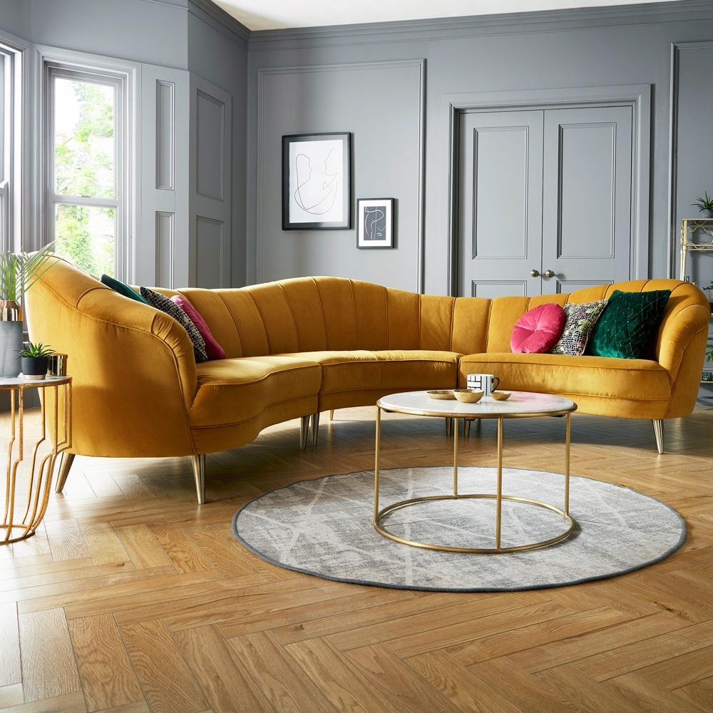 The yellow curved sofa is a playful statement in this blue-grey formal living room