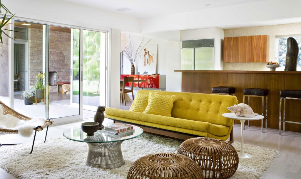 A modern tufted yellow sofa nicely contrasts with the brown cabinetry in the back