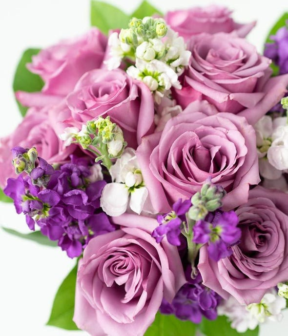 Lovely lavender roses, lavender stock, and pink stock are accented with a variety of lush greens in this amazing floral arrangement. Presented in a modern cylinder vase, the bouquet is a wonderful gift to help celebrate an anniversary, a Spring birthday, or just because.