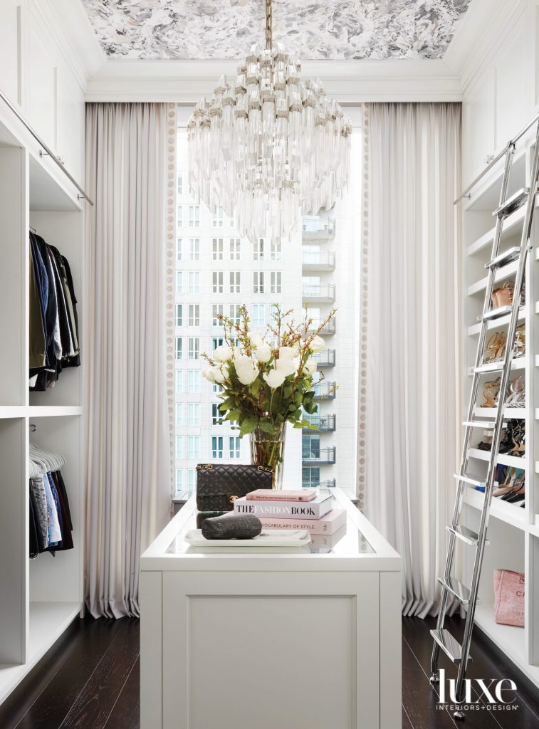 sll-white walk-in closet with drapes and chanderlier