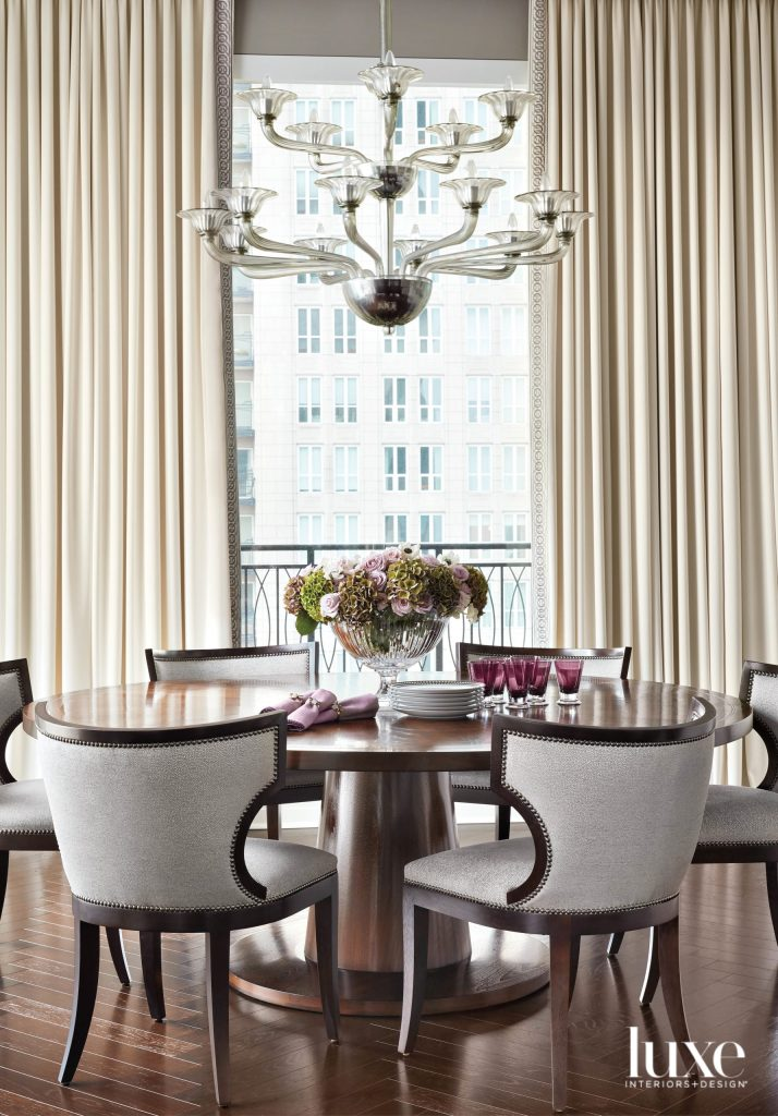 glam dining room with a wood table and crystal chanderlier
